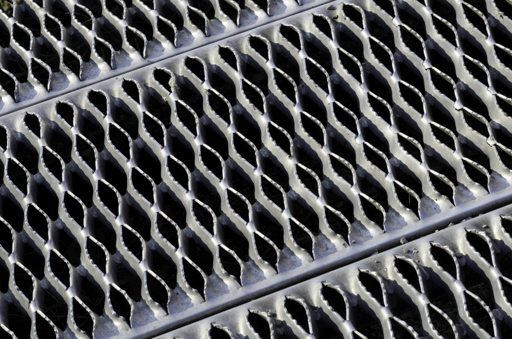 Industrial abstract Symmetrical safety ramp of aluminum with small ridges, like teeth, to provide traction for pedestrians.jpeg