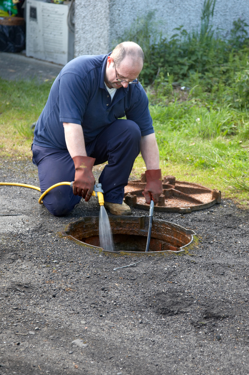 man cleaning drains